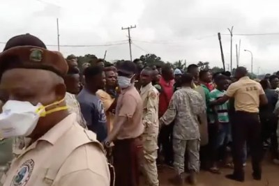 Joint security create human barricade against angry mob outside the guest house in Zwedru, where Rep. Kolubah and Mr. Cummings were staying.