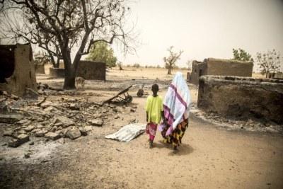 Une femme et sa fille passent devant les décombres de maisons détruites lors de l'attaque commise le 23 mars 2019 contre le village d'Ogossagou par des hommes armés dogons, au cours de laquelle 150 civils ont été tués.